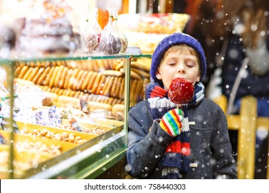 Little cute kid boy near sweet stand with gingerbread and nuts. Happy child eating on apple covered with red sugar. Traditional sweet on German Christmas market.