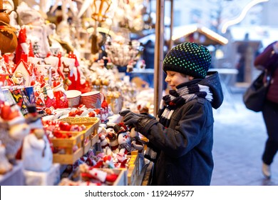 Little cute kid boy selecting decoration on Christmas market. Beautiful child shopping for toys and decorative ornaments