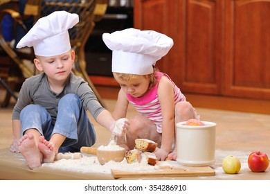 Little cute kids in chef's hats sitting on the kitchen floor, heavily soiled with wheat flour they are playing cook and having fun