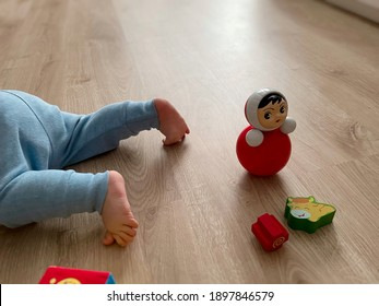 Little cute baby's legs in blue pants crawling on warm wooden floor with retro red and green toys. Baby on floor above view