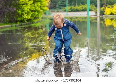 Little cute playful caucasian blond toddler boy enjoy have fun playing jumping in dirty puddle wearing blue waterproof pants and rubber rainboots at home yard street outdoor. Happy childhood concept