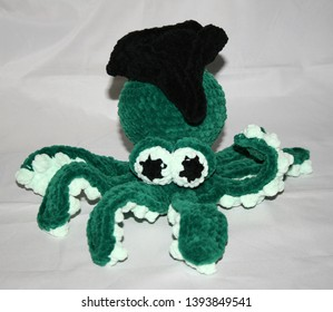 Little cute plush green octopus with black hat
