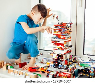 little cute preschooler boy playing constructor toys at home hap