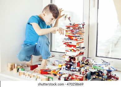 little cute preschooler boy playing lego toys at home happy smiling, lifestyle children concept