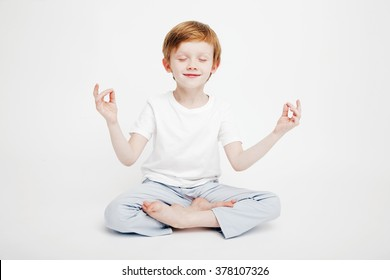 Little cute red-haired boy sitting on a white background in the