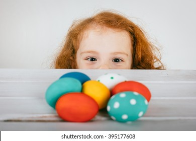 The little cute red-haired girl  is looking at Easter eggs. Toned