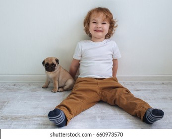 Little cute redhead curly boy in white t-shirt  with his pug puppy