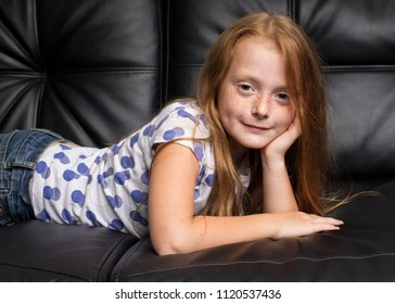 Little cute redhead girl with freckles resting on black sofa