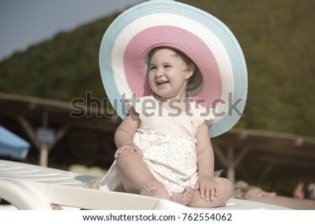 5348737e9b5 Little cute small baby girl in big hat on the sea beach. Summer season.