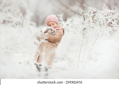 little cute smiling girl in pink hat and beige coat standing in the winter magic forest and holding a rabbit in her hands
