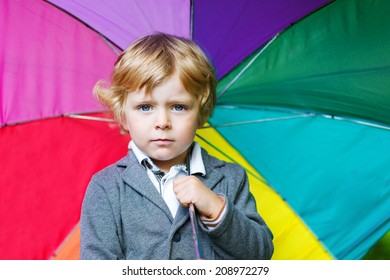 Little cute toddler boy with colorful umbrella on rainy day.