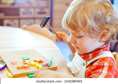 Little cute toddler boy playing with wooden puzzle hammer toys. Happy baby child playing at playschool or kindergarten. children at day care doing activity