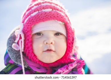 Little cute toddler girl outdoors on a sunny winter day.
