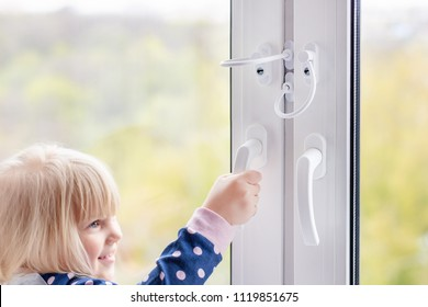 Little cute toddler girl trying to open window in apartment at high-tower building. Children window protection lock. Cable safety guard prevent opening window by child. Prevention of falling accident