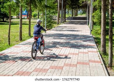 little cyclist rides through a tunnel in a park