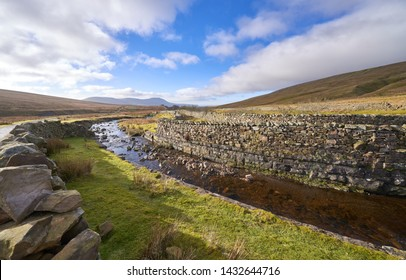 The Little Dale Beck river with the summits of Park Fell, Simon Fell and Ingleborough in the Distance. Yorkshire Dales.