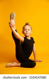 Little dancer in leotard stretching legs during workout. Full length little girl in black leotard stretching legs and looking at the camera sitting against bright yellow background during training