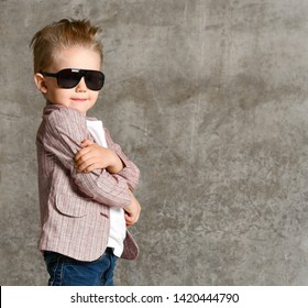 Little dandy boy in light jeans and a stylish jacket, in sunglasses on the background of a concrete wall. The child folded his arms in a closed pose on his chest. Stylish childhood