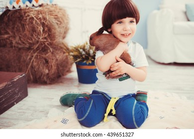 The little dark-haired boy playing in a room with a real rabbit
