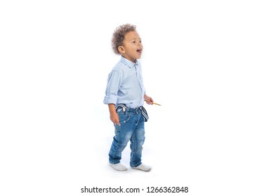 A little dark-skinned boy with curly hair in jeans and a light shirt stands in profile holding a pencil in his hands looking to the side and calling for someone