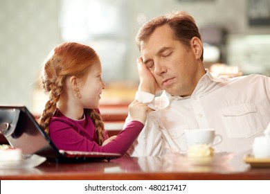 Little daughter bothering her father falling asleep in cafe