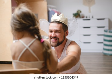 Little daughter and father have fun, dressing in princess costume, daddy makeup