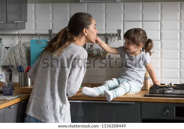 Little daughter feeding mother having fun in the kitchen at home, cute girl helping young single mom or sister playing while cooking together, mommy and kid lifestyle, funny family weekend activity