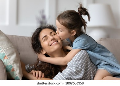 Little daughter gently cuddles kiss mother on cheek showing love and express caress resting on couch at home. Happy family, pleasure be mommy, mother day congratulations, sweet moment together concept