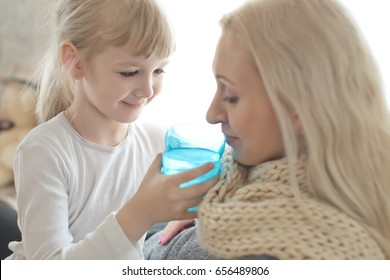Little  daughter gives to drink sick mother