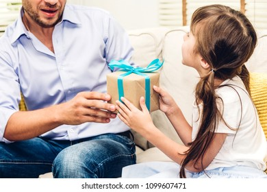 Little daughter giving her father a blue ribbon gift box for surprise at father's day.Love of family and father day concept