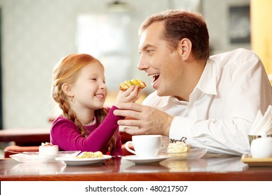 Little daughter giving pastry to her father in cafe