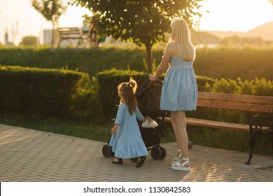 little daughter helps mom push the baby carriage. Happy family