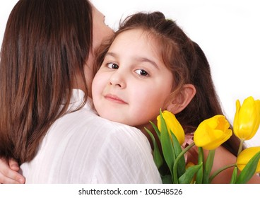 Little daughter hug her mom with bouquet of yellow tulips