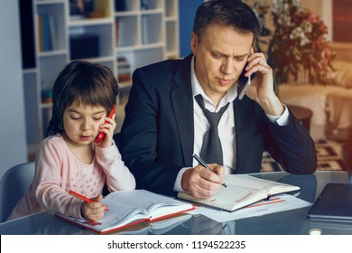 Little daughter imitate father behaviour. Writing and speaking over phone. Business at home concept.