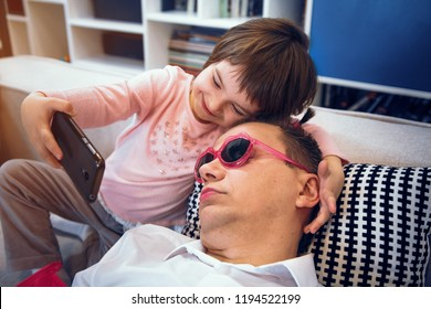 Little daughter making selfie with sleeping father after she made tails on his head and put on pink sunglasses.