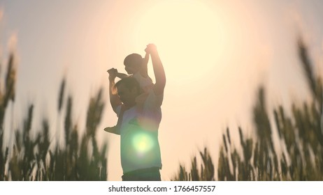 little daughter on father's shoulders. baby boy and dad travel on a wheat field. child and parent play in nature. happy family and childhood concept. Slow motion