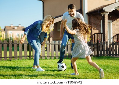 Little daughter playing soccer with her parents outside