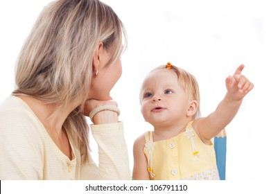 Little daughter showing to mother something isolated on white, focus on baby