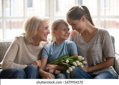Little daughter sitting between loving young mother and old grandmother on couch received white tulips, congratulation with birthday, spring holiday, gift as symbol of love attention and care concept