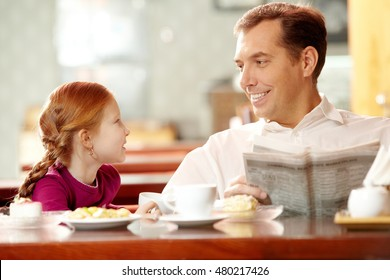 Little daughter sitting in cafe with her father