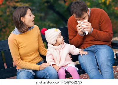 Little daughter sitting on bench in autumn park and  looking in her daddy who has a cold. Family health, colds, fall epidemics and virus epidemics