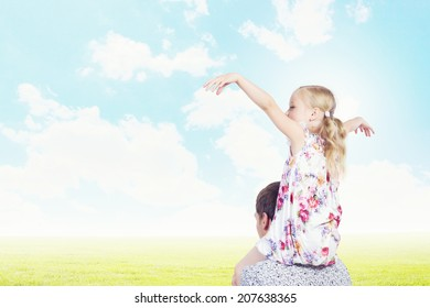 Little daughter sitting on father's shoulders. Parenting concept