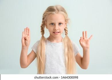 Little deaf mute girl using sign language on light background