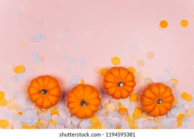 Little decorative pumpkins with confetti. Autumn and Helloween concept.