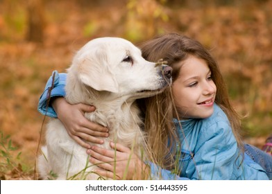 Little deochka walks in autumn forest with a dog, a golden retriever or labrador. They are having fun in the fresh air. A dog - man's best friend.