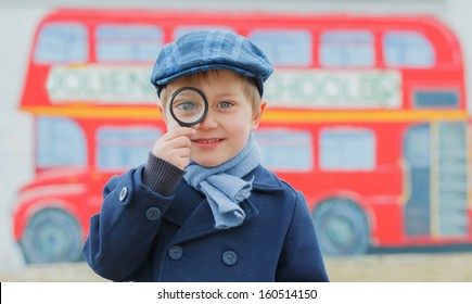 Little detective. Funny boy looking through magnifying glass near english schoolbus