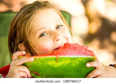 Little dirty caucasian girl eating watermelon in the sunny summer day.
