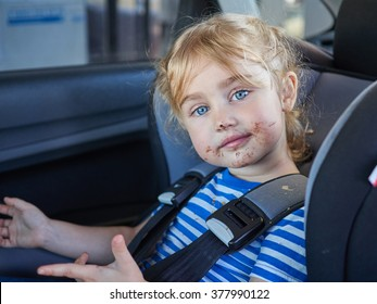 Little dirty girl , baby in a safety car seat. Safety and security