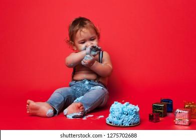 Little dirty kid, smash birhtday cake and eating