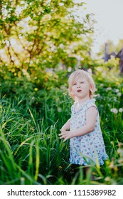 A little disgruntled girl on a beautiful green summer background in the park